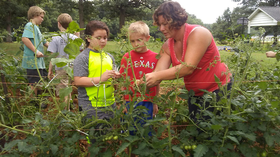 Mackenzie with children harvesting the garden