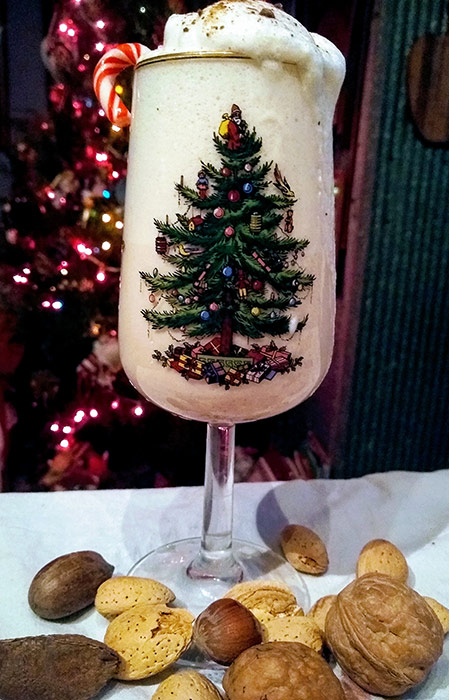 Egg nog in Christmas glass with nuts at base of glass