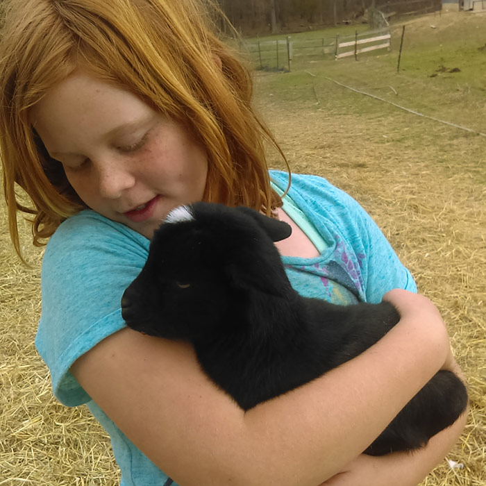 Lilly holding a black baby goat