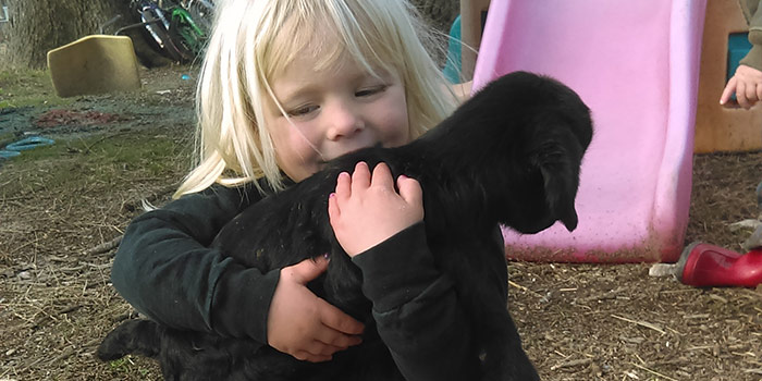 Meadow Holding A Black Baby Goat