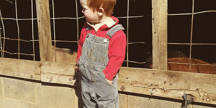 Rye Withington wearing a red shirt and shoes with blue bibbed overalls