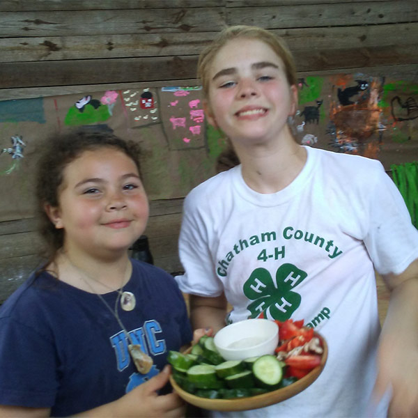 Summer camp attendees holding fresh vegetables and dip