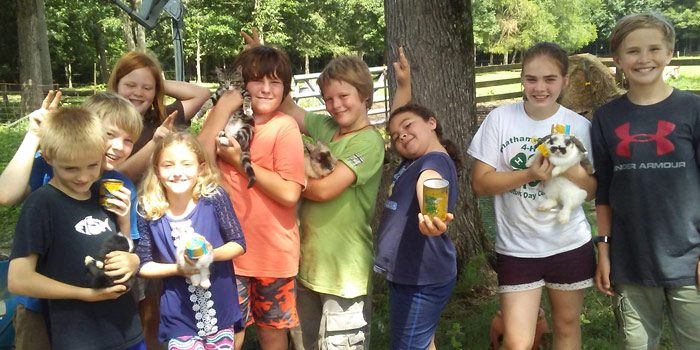 Summer Camp Attendees Holding Animals And The Crafts They Made At Camp