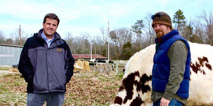 Tucker Withington And Robert Poitras Standing Outside With A Cow