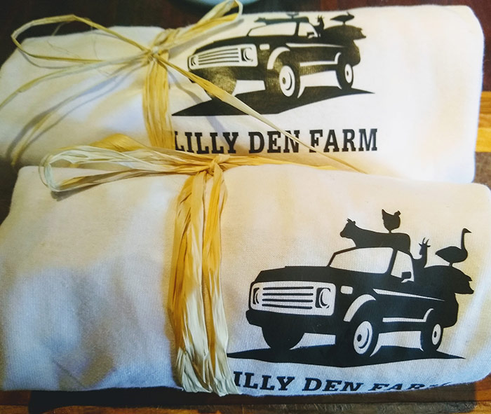 Lilly Den Farm T-Shirts rolled up and tied with straw